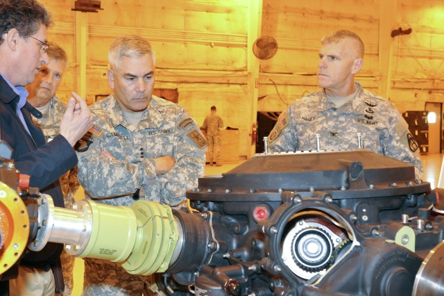 Neale Bruchman, chief of the technical management division at Program Apache, shows Vice Chief of Staff of the Army Gen. John F. Campbell a transmission from the latest iteration of the AH-64 helicopter during a visit to PEO Aviation. Maj. Gen. William T. Crosby and Col. Jeffrey Hager from PEO Aviation look on.