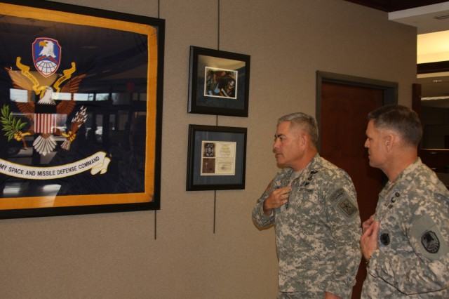 During Vice Chief of Staff of the Army Gen. John F. Campbell's visit to the U.S. Army Space and Missile Defense Command/Army Forces Strategic Command's headquarters in Huntsville, Ala., Jan. 23, Lt. Gen. David L. Mann, USASMDC/ARSTRAT commanding general, shows Campbell the command colors that flew on the International Space Station. The colors were taken into space during retired Col. T.J. Creamer's mission aboard the ISS from December 2009 through June 2010.