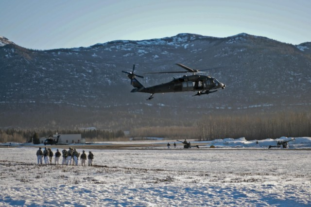 Paratroopers from Alpha Battery, 2nd Battalion, 377th Parachute Field Artillery, 4th Infantry Brigade Combat Team (Airborne), 25th Infantry Division, observe a UH-60 Black Hawk Helicopter lift a howitzer artillery gun at Bryant Army Airfield on Joint-Base Elmendorf Richardson, Alaska, Jan. 29, 2014. This training is one of many ongoing operations during the nine-day brigade-wide field training exercise to validate the Army's only active airborne force for the Asia-Pacific region. (Photo by U.S. Army Sgt. Eric-James Estrada)