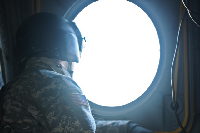 """A crew chief with Bravo Company, 1-52nd Aviation Regiment """"Sugar Bears"""" from Fort Wainwright, Alaska, observes the Alaskan landscape over Malamute Drop Zone from a CH-47 Chinook Helicopter on Joint-Base Elmendorf Richardson, Alaska, Jan. 29, 2014, during an airborne operation with paratroopers of the 4th Infantry Brigade Combat Team (Airborne), 25th Infantry Division. The airborne operation is one of many ongoing operations during a nine-day brigade-wide field training exercise to validate the Army's only active airborne force for the Asia-Pacific region. (Photo by U.S. Army Sgt. Eric-James Estrada)"""