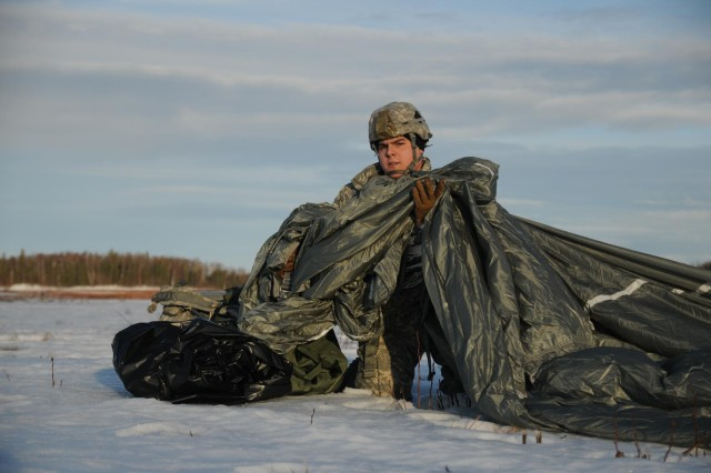 Army Pfc. Ricky Alvarez, with Apache Company, 1st Battalion, 501st Infantry Regiment, 4th Infantry Brigade Combat Team (Airborne), 25th Infantry Division, hailing from Belton, Texas, recovers his parachute after landing on the drop zone during an airborne operation Jan. 28, 2014, at the Malemute Drop Zone at Joint Base Elmendorf-Richardson, Alaska. (U.S. Army photo by Staff Sgt. Jeffrey Smith/Released)