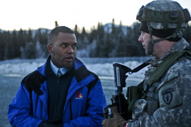 Chief Warrant Officer George Summers, of Bravo Company, 425th Brigade Special Troops Battalion, 4th Infantry Brigade Combat Team (Airborne), 25th Infantry Division, speaks with KTUU news reporter Corey Allen Young about the launching of the RQ7 Unmanned Aircraft System (UAS) on Joint Base Elmendorf-Richardson, Alaska, Jan. 30, 2014. The UAS launch is part of a larger nine-day field training exercise designed to enhance its readiness and ability to quickly respond to crisis, contingencies, and humanitarian missions in the Asia-Pacific region. (Photo by U.S. Army Sgt. Eric-James Estrada)