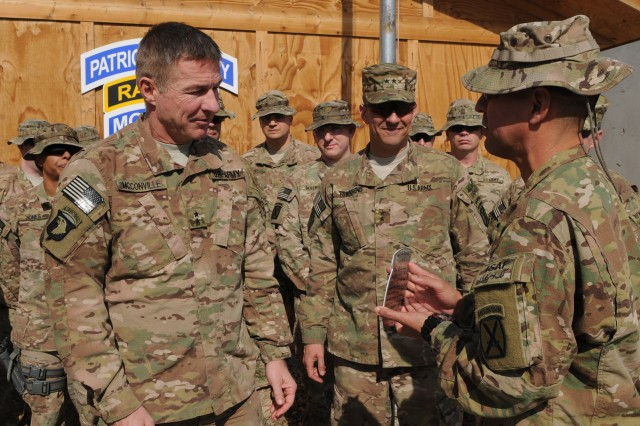 """LAGHMAN PROVINCE, Afghanistan �"""" U.S. Army Command Sgt. Maj. Noe Salinas (right) presents Maj. Gen. James McConville (left) with a locally-made 4th Brigade Combat Team, 10th Mountain Division coin during McConville�'s final visit to Forward Operating Base Gamberi, Jan. 29, 2014. Salinas serves as senior enlisted leader of 4th Brigade Combat Team, 10th Mountain Division, Task Force Patriot and presented McConville with the token of appreciation for his leadership as commander of Regional Command East�'s Combined Joint Task Force-101. (U.S. Army Photo by Sgt. 1st Class E. L. Craig, Task Force Patriot PAO)"""