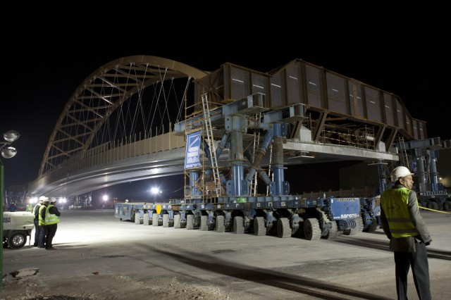 A tied arch bridge, known as the flyover bridge, was prepared to move into place over the Khalifa Bin Salman Causeway connecting Naval Support Activity (NSA) Bahrain to the U.S. Navy port facility (NSA II).  The 122.5 meter long, 21.4 meter high, 2650 metric ton bridge was constructed on NSA II, and will be driven across the causeway on self-propelled modular trailers (SPMT), and set in place on pre-constructed abutments.  The greatest benefit of this process allows Bahrain traffic to be disrupted for hours as opposed to months it would have taken to build the bridge in place.  (U.S. Navy photo by Mass Communication Specialist 1st Class Steve Smith/Released)