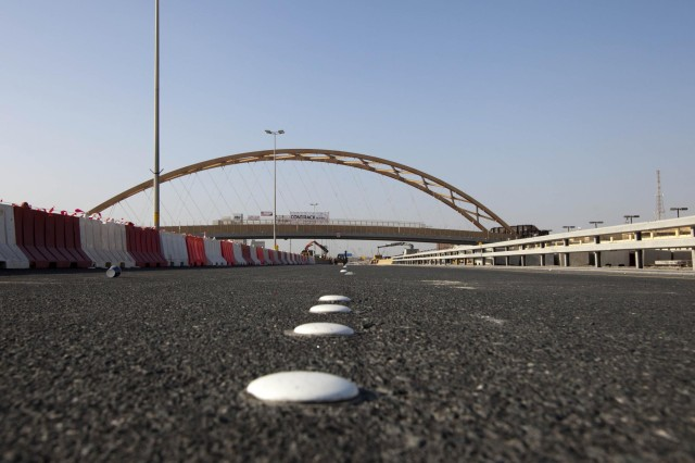 A tied arch bridge, known as the flyover bridge, was moved into place over the Khalifa Bin Salman Causeway connecting Naval Support Activity (NSA) Bahrain to the U.S. Navy port facility (NSA II).  The 122.5 meter long, 21.4 meter high, 2650 metric ton bridge was constructed on NSA II, and will be driven across the causeway on self-propelled modular trailers (SPMT), and set in place on pre-constructed abutments.  The greatest benefit of this process allows Bahrain traffic to be disrupted for hours as opposed to months it would have taken to build the bridge in place.  (U.S. Navy photo by Mass Communication Specialist 1st Class Steve Smith/Released)