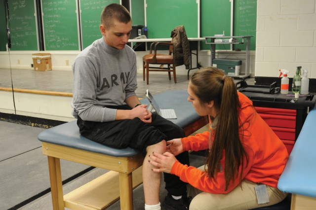 Kelsey Sheridan, a certified athletic trainer, inspects a Soldier�'s knee inside the 1st Battalion, 19th Infantry Regiment, gym.
