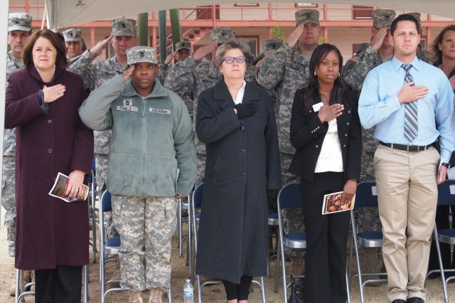 From left, Barbara Ashley, spouse of Maj. Gen. Robert Ashley, commanding general, U.S. Army Intelligence Center of Excellence and Fort Huachuca; Master Sgt. Michelle Fairley, spouse of  Sgt. Maj. Jeffery Fairley, USAICoE command sergeant major; Donna Gallagher, spouse of Brig. Gen. Peter Gallagher, acting commanding general, Network Enterprise Technology Command; Alesia Ash and Rudy Nunez, representatives of Congressman Ron Barber's office, stand during the national anthem Jan. 24 at the installation retirement ceremony on Brown Parade Field. The five were guests of honor during the ceremony.