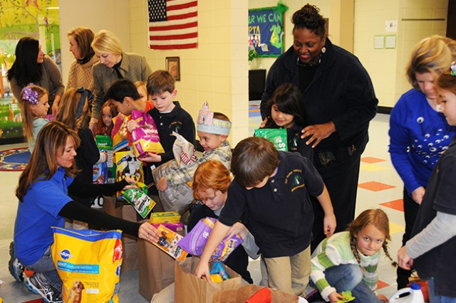 Teachers and students at the Fort Rucker Primary School organize bags of donated pet food to be taken to local animal shelters during their 100th day in school celebration Jan. 24.