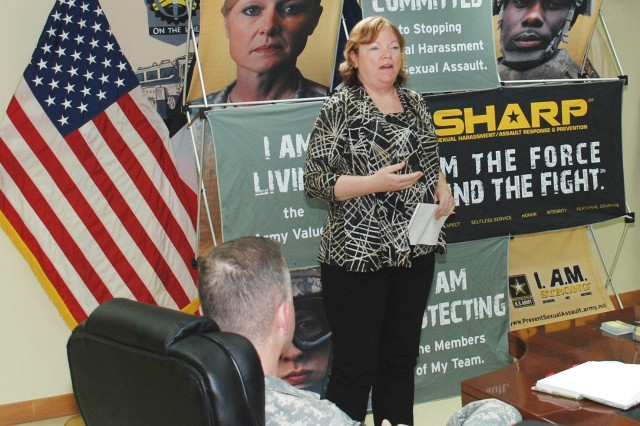 Col. James D. Kinkade, commander, 402nd Army Field Support Brigade, looks on as Jan Burke, 402nd AFSB's equal employment opportunity manager, provides information on the assistance she offers in support of the SHARP program.