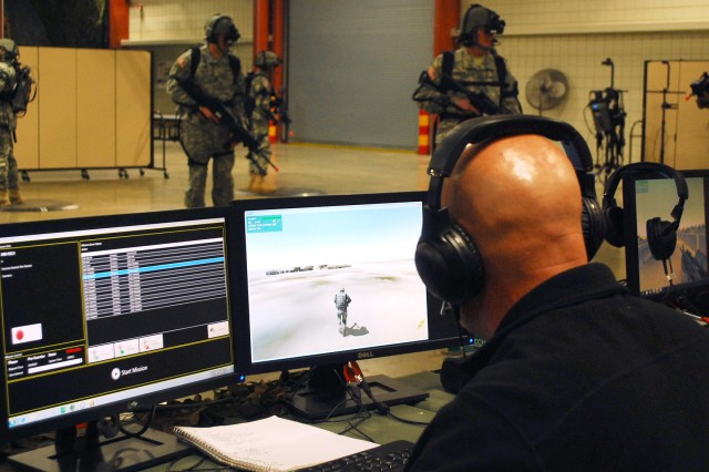 "The Dismounted Soldier Training System is a virtual simulator that will allow Cadets to practice patrolling as a squad in a town, enter and clear a building, and perform other simulated operations in mountain, desert and wooded terrain. The pads on the floor are the operational space for each Soldier. One of the benefits to the designated space is that the participants don't run into each other with their weapons while ""in the game.""  There is one exercise control station where the operator can control the scenario."