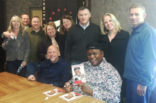 Comic legend George Wallace and fellow comedian Don Barnhart (both sitting) sign autographs for Col. Michael E. Masley (far right), commander of U.S. Army Garrison Yongsan, and some other fans after their performance at the R & R Bar and Grill, 25 Jan. The show was part of a tour produced by Armed Forces Entertainment.