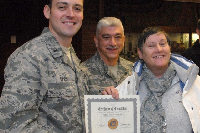 New York Air National Guard 1st Lt. Robert McCoy (left) and Chief Master Sgt. Mark Mann (middle) pose with Susan Miserandino (right) after her completion of New York's Citizen Preparedness Corps Training Program, on Staten Island, N.Y., Feb. 1, 2014. New York National Guard troops gave disaster and emergency training to more than 1,200 people who attended events at New Dorp High School here and in Suffolk County. The program is designed to give citizens the knowledge and tools to prepare for emergencies and disasters, respond accordingly, and recover as quickly as possible to pre-disaster conditions. New York National Guard troops, working with experts from the Division of Homeland Security and Emergency Services, Office of Fire Prevention and Control, and local emergency management personnel will conduct future training sessions with the goal of teaching approximately 100,000 New Yorkers during 2014. McCoy belongs to 106th Rescue Wing, Mann belongs to the 109th Airlift wing and Miserandino is a senior planning analyst for Con Edison, Inc.