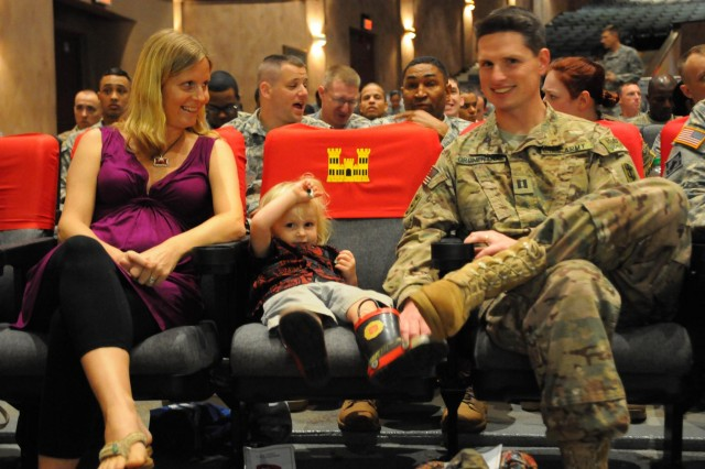 Erika Gronenthal (left), sits with her recently redeployed husband, Capt. Victor Gronenthal, the commander of the Headquarters and Headquarters Company, 130th Engineer Brigade and their young son, Kai, before being awarded the Army Engineer Association Essayons Award for her extensive work with the brigade's Family Readiness Group during a redeployment ceremony at the Schofield Barracks' Sgt. Smith Theater, Feb. 3.