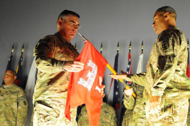 The command team of the 14th Construction Management Team, 130th Engineer Brigade, Lt. Col. Richard Collins (left) and Sgt. Maj. Brande Small (right), uncase their unit's colors during a redeployment ceremony signifying the official return of their unit and its soldiers, Feb. 3, at the Sgt. Smith Theater on Schofield Barracks.