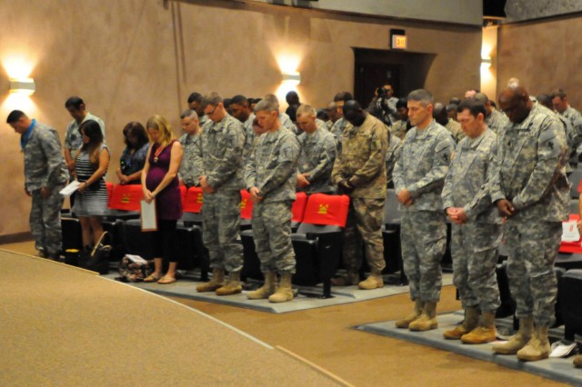 The command for the 8th Theater Sustainment Command stands and honors those recently redeployed soldiers from the 14th Construction Management Team and the 15th Explosive Hazards Team, Feb. 3, during a redeployment ceremony at the Sgt. Smith Theater on Schofield Barracks.