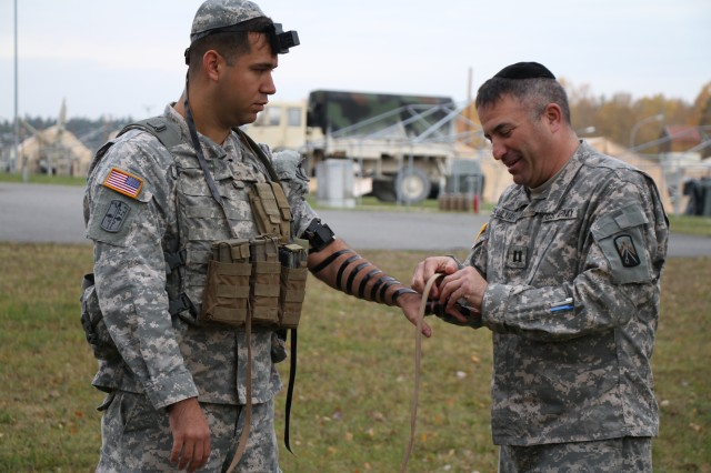 "Army Jewish Chaplain Capt. Andrew Shulman, 18th Combat Sustainment Support Battalion, wraps leather straps and �""tefillin"" around Sgt. Zachary Gardner�'s arm before praying. For centuries, Jews have strapped these small leather boxes containing parchments of scriptures from the Torah onto their arms and head. This ritual has often been seen as a sign of faith and remembrance. Gardner is an infantryman in U.S. Army Garrison Bavaria with the 7th Army Joint Multinational Training Command."