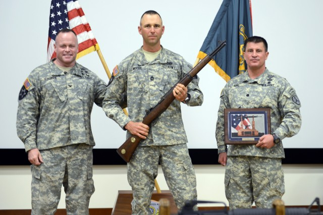 Army Reservist Master Sgt. Russell Moore (center) holds a Secretary of the Army M1 Garand Trophy Rifle after winning his fifth overall U.S. Army Small Arms Championship, Feb. 1, 2014, at Fort Benning, Ga. Moore came out on top after a week of rifle, pistol and combined arms matches with more than 210 Soldiers from the force. He is pictured with Col. Robert Choppa, Infantry School commandant, and Lt. Col. Don King, U.S. Army Small Arms Championship commander.