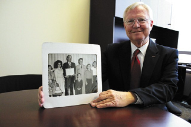 """Jim Henderson, who knew Dr. John McDaniel throughout his life, holds a photo of McDaniel receiving an award from Maj. Gen. John Zierdt.  with McDaniel is his family, including, from left, daughter Bonnie, wife Helen """"Johnnie,"""" and sons Willie, Mark and John Jr."""