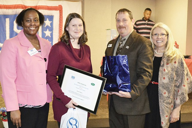 April Rogers, second from left, poses for a photo with the award and gifts she received in recognition of her selection as a United Service Organization Volunteer of the Year during a Jan. 25 celebration in Richmond. Also pictured is Kasinda Thomas, left, director of the Fort Lee USO Center; Jeff Heckert, a USO of Hampton Roads and Central Virginia financial sponsor; and Paula Moran, president and CEO of USOHRCV.