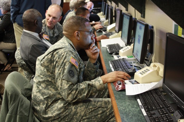 Chaplain (Col.) James Palmer, installation chaplain, checks Facebook for questions at the Emergency Operations Center during a garrison town hall meeting Tuesday.