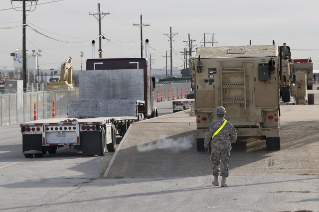 """A Soldier assigned to the 1st �""""Ironhorse"""" Brigade Combat Team, 1st Cavalry Division guides an M1113 Expanded Capacity High Mobility Multi-purpose Wheeled Vehicle onto a concrete ramp before being loaded onto an 18-wheeler flatbed truck during line haul operations, Jan. 29, at Fort Hood, Texas. Ironhorse conducted line haul operations, a process to move equipment by truck, for the upcoming rotation to the National Training Center. (U.S. Army photo by Pfc. Paige Pendleton, 1st BCT PAO, 1st Cav. Div.)"""