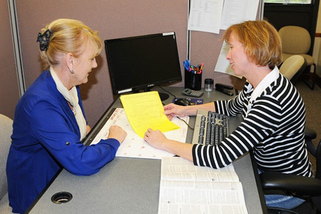 Gaile Avelyn and Erin McGlone, tax preparers at the Tax Center, go over tax forms at the tax center offices in Bldg. 5700 last year. The tax center is open Mondays-Fridays from 9 a.m. to 4 p.m. through April 15, and help is available by appointment only.