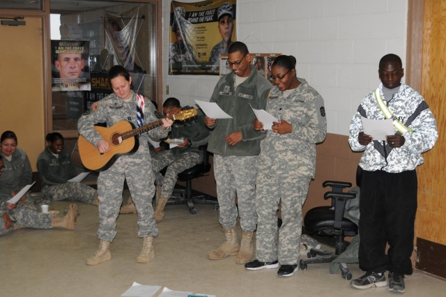 Chaplain (Capt.) Tanya Bindernagel, 168th Brigade Support Battalion chaplain, plays a guitar as her choir leads in the singing of spiritual hymns. The unit ministry team hosted Operation Spiritual Fix-it Jan. 30, 2014, to boost Soldier resiliency and maintain unit readiness through spiritual fitness.