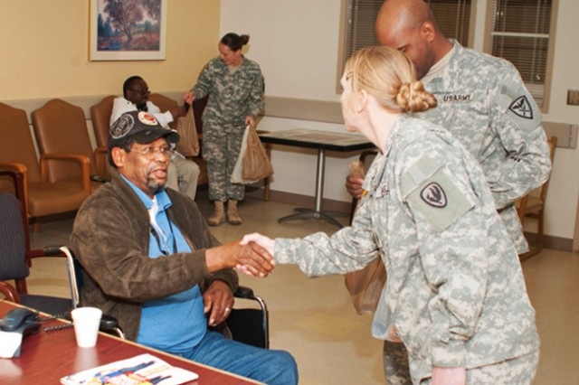 First Sgt. Gloria Cain, NCO Academy deputy commandant, shakes the hand of a veteran Jan. 31 at Central Alabama Veterans Health Care System Home when a group of Soldiers went to visit and take them needed goods.