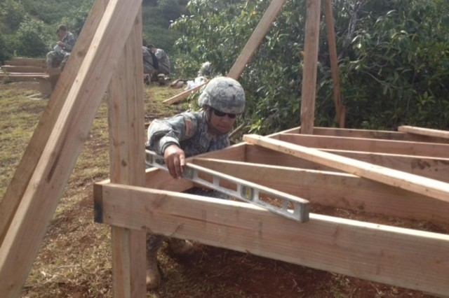 Chief Warrant Officer 2 LaJuye Hackley, a soldier with the 643rd Engineer Company, 84th Engineer Battalion, 130th Engineer Brigade, 8th Theater Sustainment, ensures that the floor system is level and plum before decking and walls are installed Jan. 22-29 in remote areas throughout the Kahuku Training Area Command in support of the 25th Infantry Division's Jungle Operations Training Center. (U.S. photo by 1st Lt. Tyler Skomp, 2nd Platoon, 643rd Engineer Company (Vertical), 84th Engineer Battalion, 130th Engineer Brigade, 8th Theater Sustainment Command)