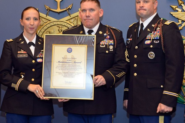 Members of Company D, 3rd General Support Aviation Battalion, 82nd Combat Aviation Brigade pose with the Secretary of Defense Award for Maintenance Excellence, Field-Level, Medium Category, during a ceremony at the Pentagon, Feb. 5. The award recognizes outstanding performance in Army field-level and depot-level maintenance. (L-R) Capt. Kimberly Shelton and Sgt. 1st Class John Bloyd, and 3-82 GSAB Command Team, Lt. Col. William Braman. The unit went on to win the Phoenix award, which recognizes the �'best of the best�' in Army maintenance excellence.