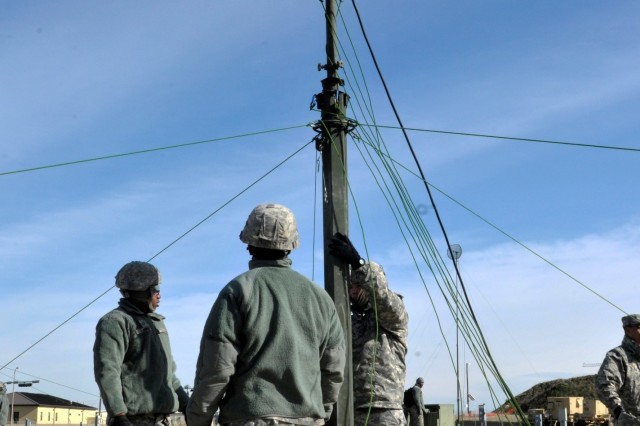 Pfc. Jason Burton (left), and Pfc. Oscar King (right), both High Capacity Line of Sight team members assigned to 2nd Battalion, 82nd Field Artillery Regiment, 3rd Brigade Combat Team, 1st Cavalry Division, receive assistance while raising the HCLOS antenna Jan. 28 at Fort Hood, Texas. The HCLOS teams participated in a validation exercise meant to familiarize the HCLOS teams with the equipment and ensure they can provide communications. (U.S. Army photo by Sgt. Brandon Banzhaf, 3rd BCT PAO, 1st Cavalry Division)