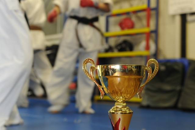 Risa Sudo, background, a master labor contract employee assigned to the 403rd Army Field Support Battalion-Northeast Asia at Sagami General Depot, practices karate with her students at the Sagamihara Suzuki martial arts dojo. The trophy and medal Sudo received for winning in her weight class at the 27th European Karate Kyokushin Championships held in November 2013 in Legnica, Poland, are seen in the foreground.