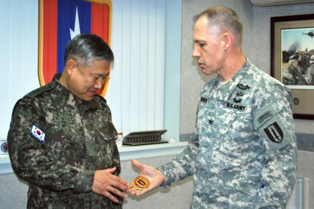 Col. Paul H. Fredenburgh III, commander, 1st Signal Brigade, gives ROKA Brig. Gen. Song Kyung-ho, assistant chief of staff, C6, Combined Forces Command, a 1st Signal Brigade coin to express his appreciation for his visit at USAG Yongsan, South Korea Jan. 24, 2013.  (U.S. Army Photo by CPL Jong Soo Oh)