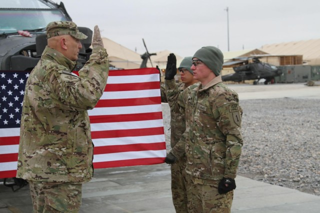Gen. Raymond T. Odierno, chief of staff of the Army, re-enlists Sgt. Justin Schreiner, an AH-64 attack helicopter repairer with 1st Infantry Division's 1st Combat Aviation Brigade, at Kandahar Airfield, Feb. 7, 2014. Odierno was in southern Afghanistan with Baltimore Ravens head coach John Harbaugh to meet with deployed service members.