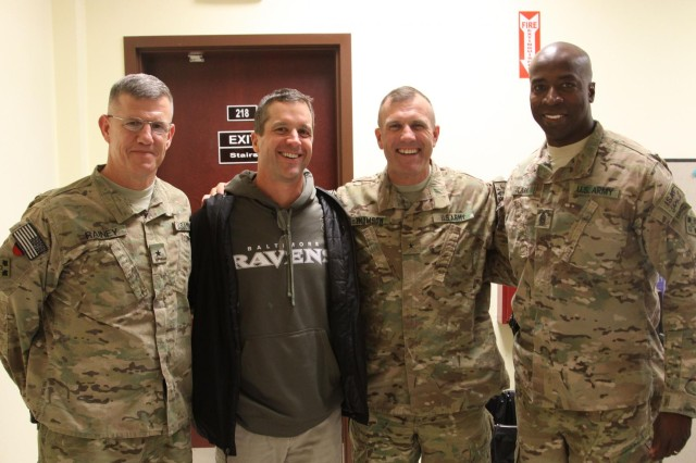Brig. Gen. James E. Rainey, 4th Infantry Division and Regional Command (South) deputy commanding general for maneuver; Baltimore Ravens head coach John Harbaugh; Brig. Gen. John Thomson, 4th Infantry Division and Regional Command (South) deputy commanding general for support; and Command Sgt. Maj. David M. Clark, 4th Infantry Division and Regional Command (South) senior enlisted adviser, pose for a photo at Kandahar Airfield, Afghanistan, Feb. 6, 2014. Harbaugh was in southern Afghanistan with Gen. Ray Odierno, chief of staff of the Army, to visit deployed service members and thank them for their service.