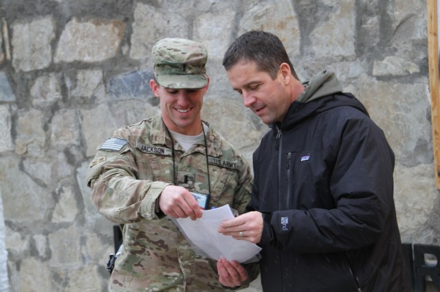 Baltimore Ravens head coach John Harbaugh signs a photo for 1st Lt. Andrew Jackson, an aide-de-camp in Regional Command (South), at Kandahar Airfield, Afghanistan, Feb. 6, 2014. Harbaugh was in southern Afghanistan with Gen. Ray Odierno, chief of Staff of the Army, to visit deployed service members and thank them for their service.
