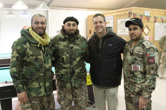Baltimore Ravens head coach John Harbaugh poses for a photo with Jordanian service members at Kandahar Airfield's Morale, Welfare and Recreation Game Room, in Afghanistan, Feb. 6, 2014. Harbaugh was in southern Afghanistan with Gen. Ray Odierno, chief of staff of the Army, to visit deployed service members and thank them for their service.