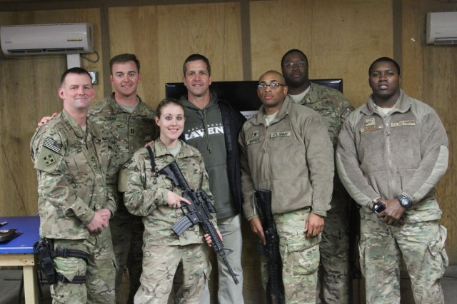 Baltimore Ravens head coach John Harbaugh poses for a photo with service members at Kandahar Airfield's Morale, Welfare and Recreation Game Room, in Afghanistan, Feb. 6, 2014. Harbaugh was in Afghanistan with Gen. Ray Odierno, chief of staff of the Army, to visit deployed service members and thank them for their service.