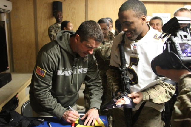 Baltimore Ravens head coach John Harbaugh signs a flag for a service member at Kandahar Airfield's Morale, Welfare and Recreation Game Room in Afghanistan, Feb. 6, 2014. Harbaugh was in southern Afghanistan with Gen. Ray Odierno, chief of staff of the Army, to visit deployed service members and thank them for their service.