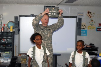 Chief Warrant Officer 2 Paul Craig, Company C, 2nd Battalion, 3rd Aviation Regiment, 3rd Combat Aviation Brigade, talks about a day in the life of an Army Helicopter pilot to two students at the Starbase Academy on Hunter Army Airfield Feb. 6. The St...