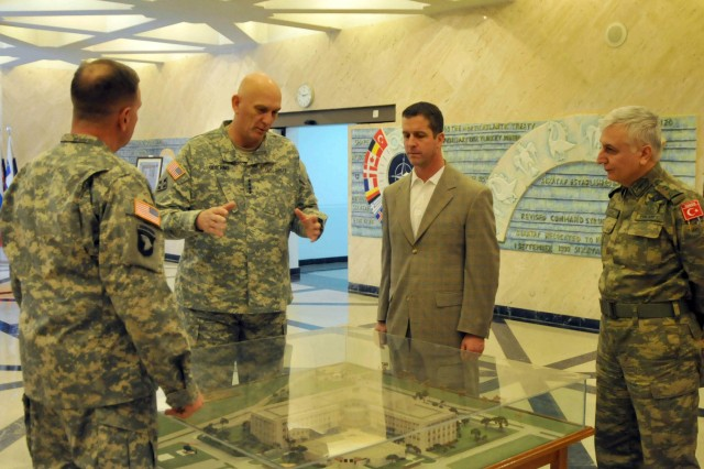 "Lt. Gen. Frederick ""Ben"" Hodges, LANDCOM commander; Chief of Staff of the Army Gen. Ray Odierno; John Harbaugh, head coach of the Baltimore Ravens; and Turkish Army Maj. Gen. Ugur Tarcin, LANDCOM chief of staff, review a scale model of the new LANDCOM facility in Izmir, Turkey. Odierno visited Izmir to get a LANDCOM status update briefing and to emphasize his belief in the need for continued U.S. Army interoperability across NATO. Harbaugh was along to meet and greet U.S. service members in Turkey."