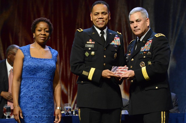 Vice Chief of Staff of the Army Gen. John F. Campbell (right) presented Brig. Gen. C. David Turner with a recognition award during the 9th Annual Stars and Stripes recognition dinner, part of the 2014 Black Engineer of the Year STEM conference, Feb. 7, 2014, in Washington, D.C.  Turner's wife, Marsha, appeared with him on stage.