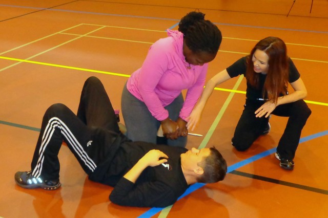 During a visit to RAF Mildenhall on Feb. 4, 2014, Linda Vu leads a participant through the process of disarming an attacker, played here by Damon Canady.