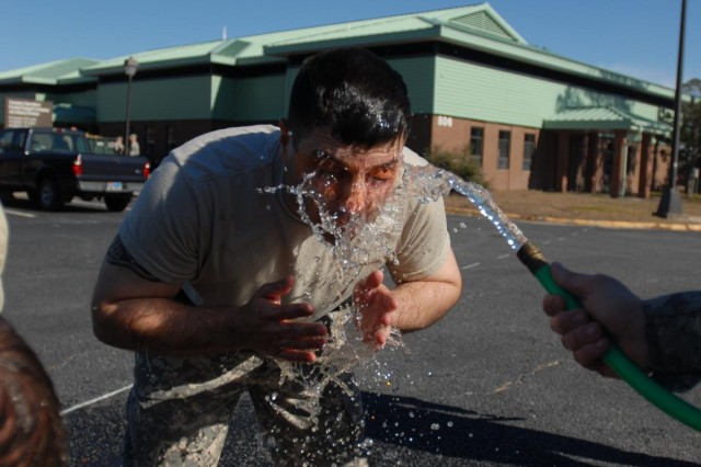 Spc. Joshua Willison, a Hemet, Calif., native and a military police officer with the military police platoon of Headquarters and Headquarters Company, 4-3 Brigade Special Troops Battalion, 4th Infantry Brigade Combat Team, 3rd Infantry Division, washes oleoresin capsicum spray from his face after completing a law enforcement certification course on Fort Stewart, Ga., Jan. 31, 2014. The OC spray causes a burning, painful sensation to give MPs a real-life experience of one of the non-lethal levels of force they have at their disposal. (U.S. Army Photo by Sgt. Joshua Laidacker, 4th IBCT, 3rd ID, Public Affairs)