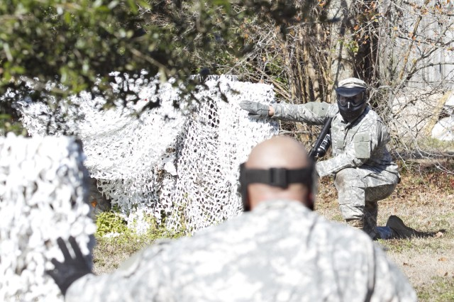 Staff Sgt. William Hall uses hand and arm signals to effectively communicate with his team mate, Staff Sgt. Jerry Camacho during their unit's battle assembly training. Both Soldiers are drill sergeants with Co. A 1/321st Infantry Regiment, 98th Training Division, 108th Training Command (IET). The unit utilized paintball training in order to bring a heightened sense of realism to the training on February 8 at the Charleston Air Force Base recreation area in Charleston, S.C.