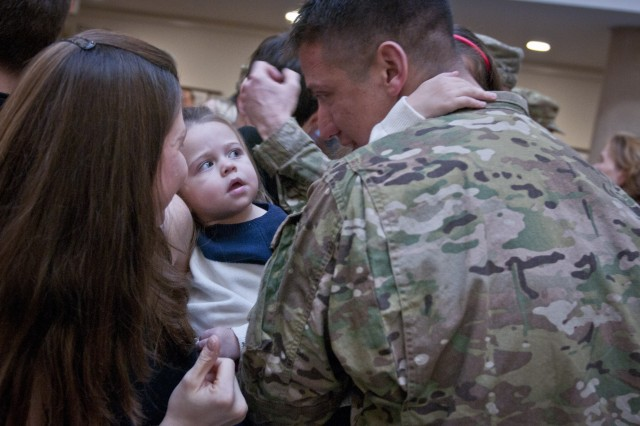 Charlotte Settles gazes at her dad, 1st Lt. James Settles, during the welcome home ceremony for Headquarters and Headquarters Company, III Corps, Feb. 9, 2014.  Soldiers with the HHC returned from a nine-month deployment to Afghanistan. (U.S. Army photo by Sgt. Ken Scar, 7th Mobile Public Affairs Detachment)