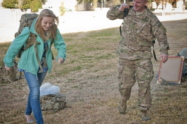 Hannah Norwood helps her dad, Col. Paul Norwood, tote his gear to their car after his return from a nine-month deployment to Afghanistan with Headquarters and Headquarters Company, III Corps, Feb. 9, 2014. (U.S. Army photo by Sgt. Ken Scar, 7th Mobile Public Affairs Detachment)