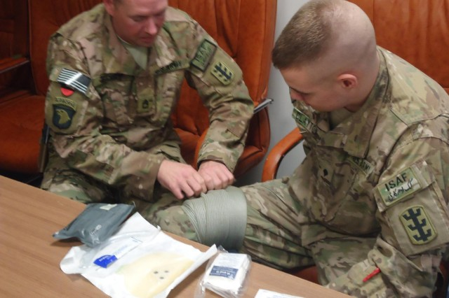 Sgt. 1st Class Eric Perry (left), JTF Sapper Operations NCO, places a pressure dressing on Spc. Justin Clayton, a signal support specialist, during a medical training refresher course at New Kabul Compound, Jan. 30.  The unit recently went over training on basic skills after reaching their halfway mark in their nine month deployment to Afghanistan, to ensure Soldiers were staying vigilant and prepared. (U.S. Army photo by 1st Lt. Bryan Pruitt, JTF Sapper)