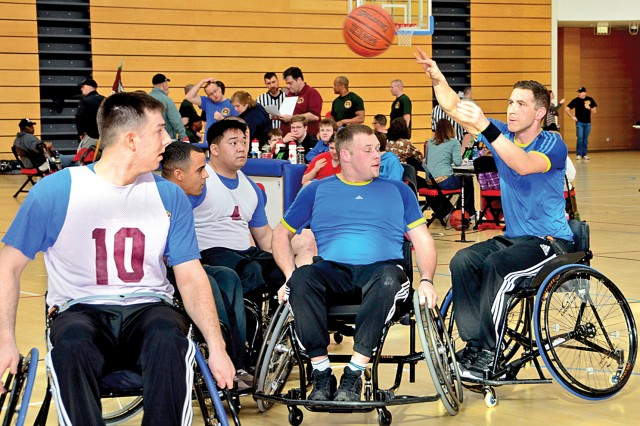 Kai Cziesla, a German Bundeswehr Soldier, makes a pass over the Warrior Transition Unit company A players during adaptive wheelchair basketball action at the Wiesbaden Fitness Center, in Germany, Feb. 6, 2014, as part of the Warrior Transition Battalion-Europe Commander's Cup Challenge.