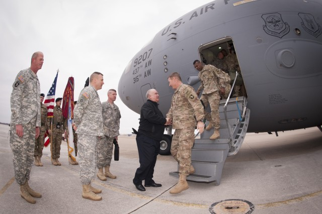 Under Secretary of the Army Joseph W. Westphal (center) greets Maj. Gen. James C. McConville (right), commander of the 101st Airborne Division (Air Assault) and Fort Campbell, Ky., as the division command group arrives at Campbell Army Airfield, Feb. 7, 2014, after a year-long deployment in Regional Command-East at Bagram Airfield, Afghanistan. Westphal praised the division's accomplishments and recognized the important role they played in overseeing the transition of authority and responsibility for Afghanistan's security throughout Regional Command-East to the Afghan National Army.